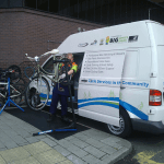 Mechanic working on a bicycle with the Watford Cycle Hub mobile workshop van